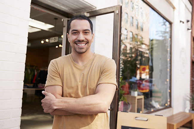 Young Hispanic shop owner smiling to camera